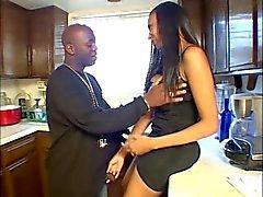 Ebony slet geeft haar vriend een blowjob in de keuken