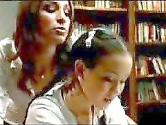 Colegiala en Skirt Cómo una palmada de otra chica en la biblioteca de