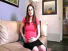 Zwangere brunette doet een striptease en poses naakt op de bank