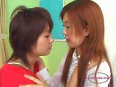 2 Asiatiska tjejer kyssas passionerat sugande tungor på sängen