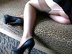Del bebé en stockigs y zapatos de tacón en un lecho