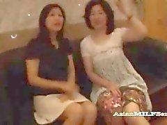 2 Mogna asiatiska kvinnor sugande Guy Jerking Off hans kuk på sängen i hotellet