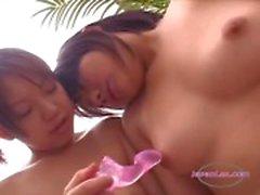 2 Aziatische meisjes stimuleren hun tepels Met Speelgoed Op De Bank