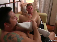 Handsome jock sniffs and licks his friends feet and wanks