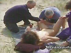 O sexo em grupo exterior na praia