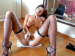 Leggy brunette rubs her pussy in fishnet stockings