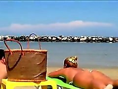Плотного Белая женщина Tanning At The Beach