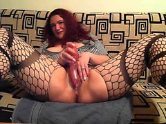 Chubby redhead in fishnet stockings fondles her big tits an