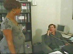 Zwangere ebony neemt witte haan in het kantoor