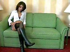 Amateur brunette in laarzen en zwarte kousen doet een kerel op een groene bank