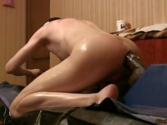 A boy in oil, fucks a huge black dildo with his little hole