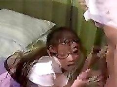 colegiala linda que se sienta en la cama mientras ella le da un blowj