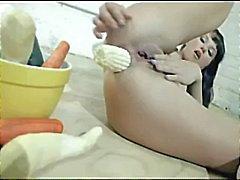 Brunette besluit om een salade te maken in haar kont met een kom van groenten
