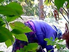 Granny pesee old pillua metsässä tien läheisyydessä